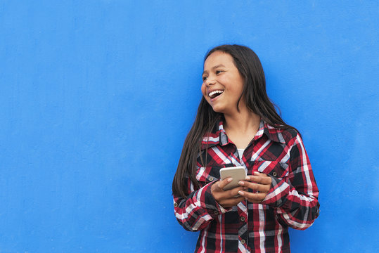 Portrait of beautiful latino girl using the mobile in the street.