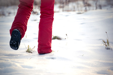 walking in the freezing winter on snow in red trousers and snow boots.