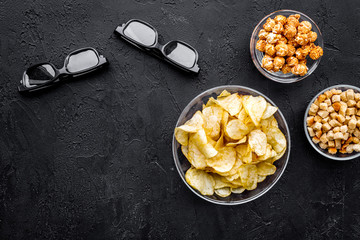 Cinema food. Crisp, popcorn, rusks near glasses on black background top view copyspace