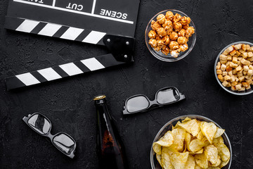 Crisp, popcorn, rusks for watching film. Clapperboard and glasses on black background top view