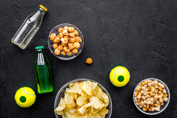 Snacks for watching sport matches and games on TV. Crisps, popcorn, rusks near drink and ball on black background top view copyspace