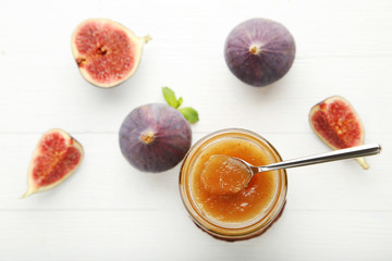 Fig jam in glass jar with spoon on wooden table