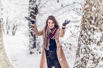 beautiful young woman enjoying her afternoon or morning outdoors in beautiful snowy nature in winter