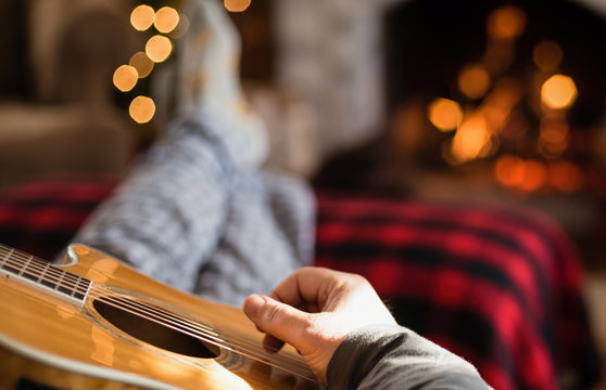 Closeup of man's hand strumming guitar with feet up in front of a cozy fire