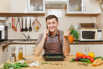 Man in apron sitting at table with vegetables, dill, talking on mobile phone, cooking at home preparing meat stake from beef or lamb, in light kitchen with wooden surface, full of fancy kitchenware.