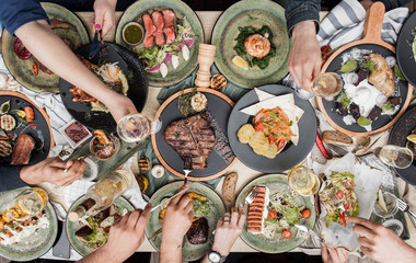 beautifully served table with different restaurant dishes and hands with glasses of wine