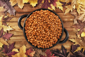 Overhead photo of a pot of baked beans on a wooden table and autumn fall leaves in the background.