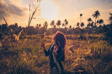 sunset portrait of beautiful young woman on a field