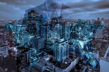 Double exposure of businessman with cityscape blue tone city scape and network connection concept