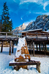 wooden shelter for boats in the mountain lake with mountains and blue sky