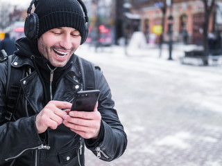 Smiling man walking in the city by the winter and listening to the music via headphones connected to thhe phone bu bluetooth