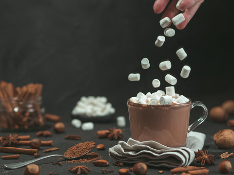 Marshmallows falls from hand in glass mug with hot chocolate cocoa drink. Copy space. Winter food and drink concept. Flying marshmallow. Dark background. Low key.
