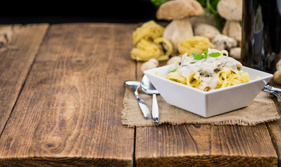 Porcini pasta on wooden background; selective focus