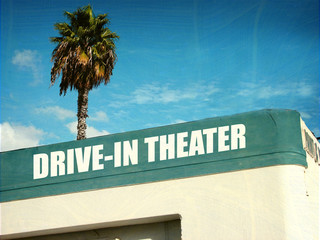 aged and worn drive in tehater sign with palm trees