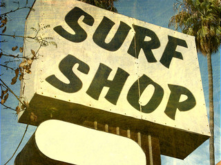 aged and worn surf shop sign with palm trees