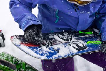 Woman freerider installs splitboard, in snow wild mountains