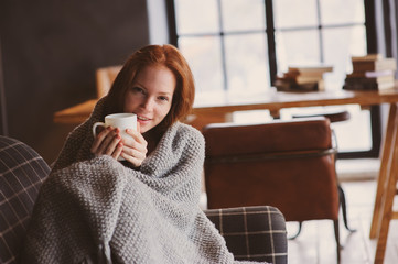 young sick woman healing with hot drink at home on cozy couch, wrapped in knitted blanket