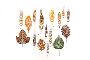 A lot of autumn dry leaves with white hand-drawn ethnic patterns. Isolated. Top view.