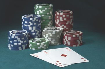 Poker chips and two A A cards on green table
