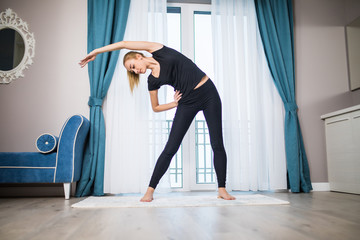 Woman doing yoga exercise at home. Morning workout in bedroom. Healthy and sport lifestyle.