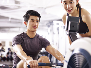 young asian couple working out using rowing machine