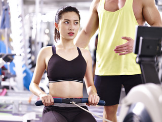 young asian adult woman exercising using rowing machine