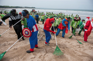 Workers wearing super hero costumes to attract tourists, sweep up garbage at Kuta Beach, Bali