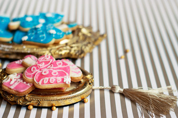 Close up of homemade pink Christmas or winter cookies served on vintage golden picture frame or trail, copy space
