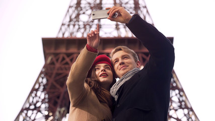 Happy loving couple of tourists doing selfie on background of Eiffel Tower