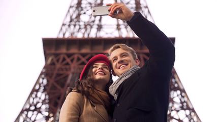 Happy man and woman smiling and posing for selfie in Paris, vacation memories