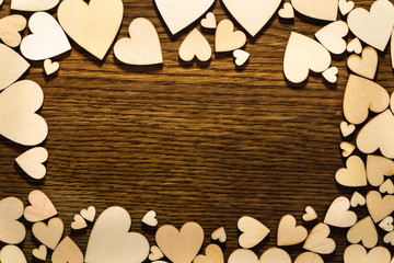 Love frame with light hearts around and dark wooden background in the middle