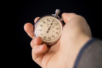 Man holding Vintage stopwatch on black background