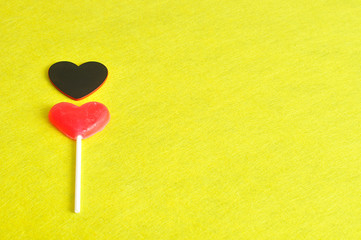 Valentines day. A red heart shape lollipop with a black heart isolated against a yellow background