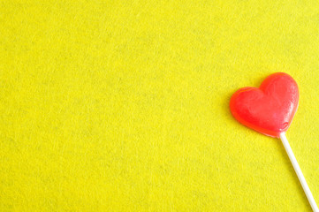 Valentines day. A red heart shape lollipop isolated against a yellow background