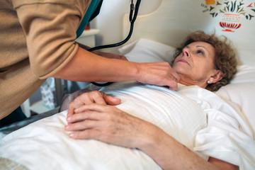 Unrecognizable female caregiver auscultating senior woman at home