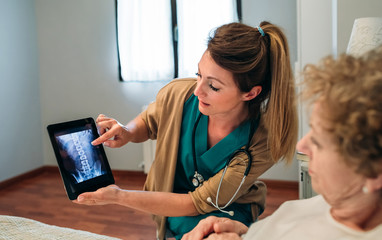 Female doctor showing to female senior patient an x-ray on the tablet