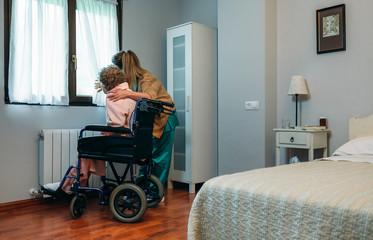 Caregiver showing the view through the window to an elderly patient in a wheelchair