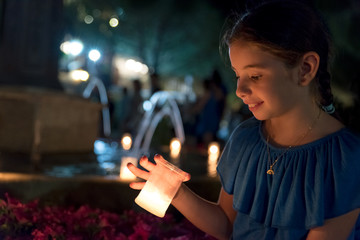Little girl lit by lit candles during a large celebration in the village square of Navacerrada, Spain.