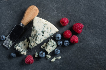Blue cheese with fresh berries on stone dark black background. French food concept. Top flat view, from above.