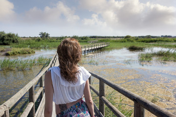 Young woman posing on a wooden bridge on the nature background. Travel, Freedom, Lifestyle concept.