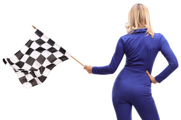 Rear shot of a woman in a racuing suit waving a checkered race flag