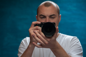 Close-up of blurred unidentified young man photographer with camera in his hands taking pictures on blue background
