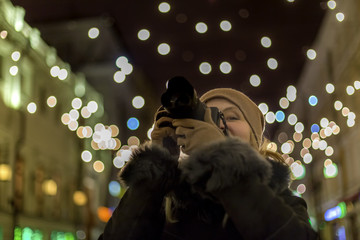 Woman photographer makes photos in the night city