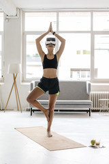 Young woman practising yoga wearing VR glasses