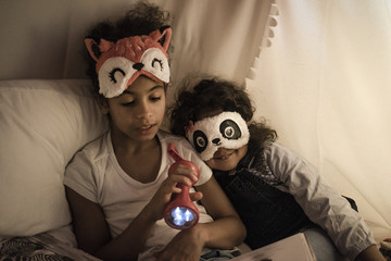 Two sisters sitting in dark children's room, playing with torch, reading book