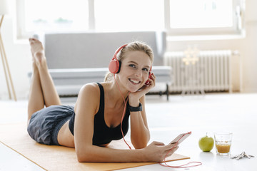 Smiling young woman in sportswear lying on gym mat listening to music