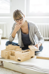 Woman in office looking at architectural model