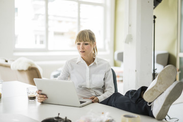 Businesswoman using laptop in office with feet on desk