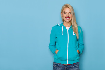 Smiling Blond Woman In Turquoise Blouse Is Posing With Hands In Pocket