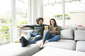 Couple sitting on couch reading book